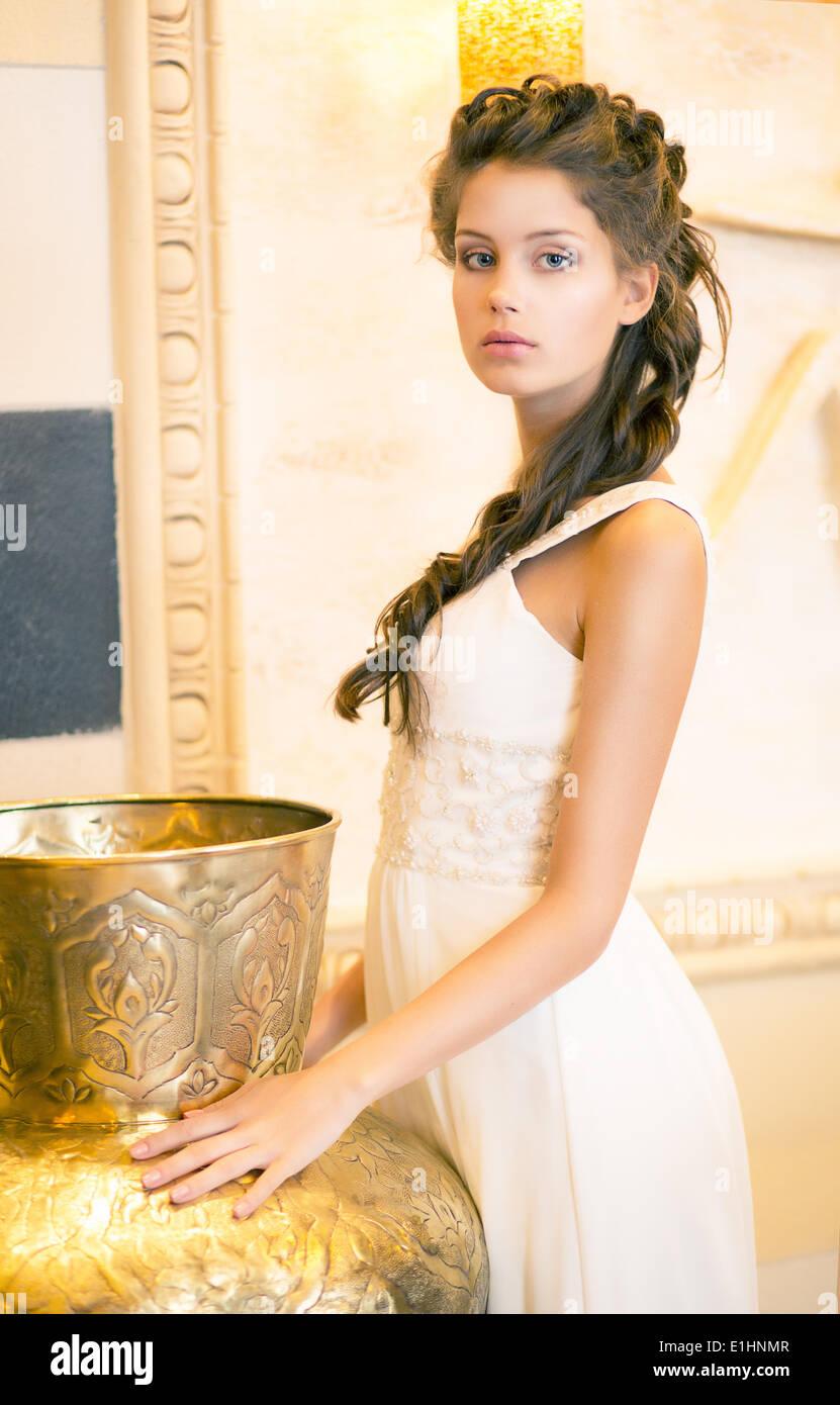 Luxurious Posh Brunette in White Dress. Oriental Antique Golden Decor - Stock Image
