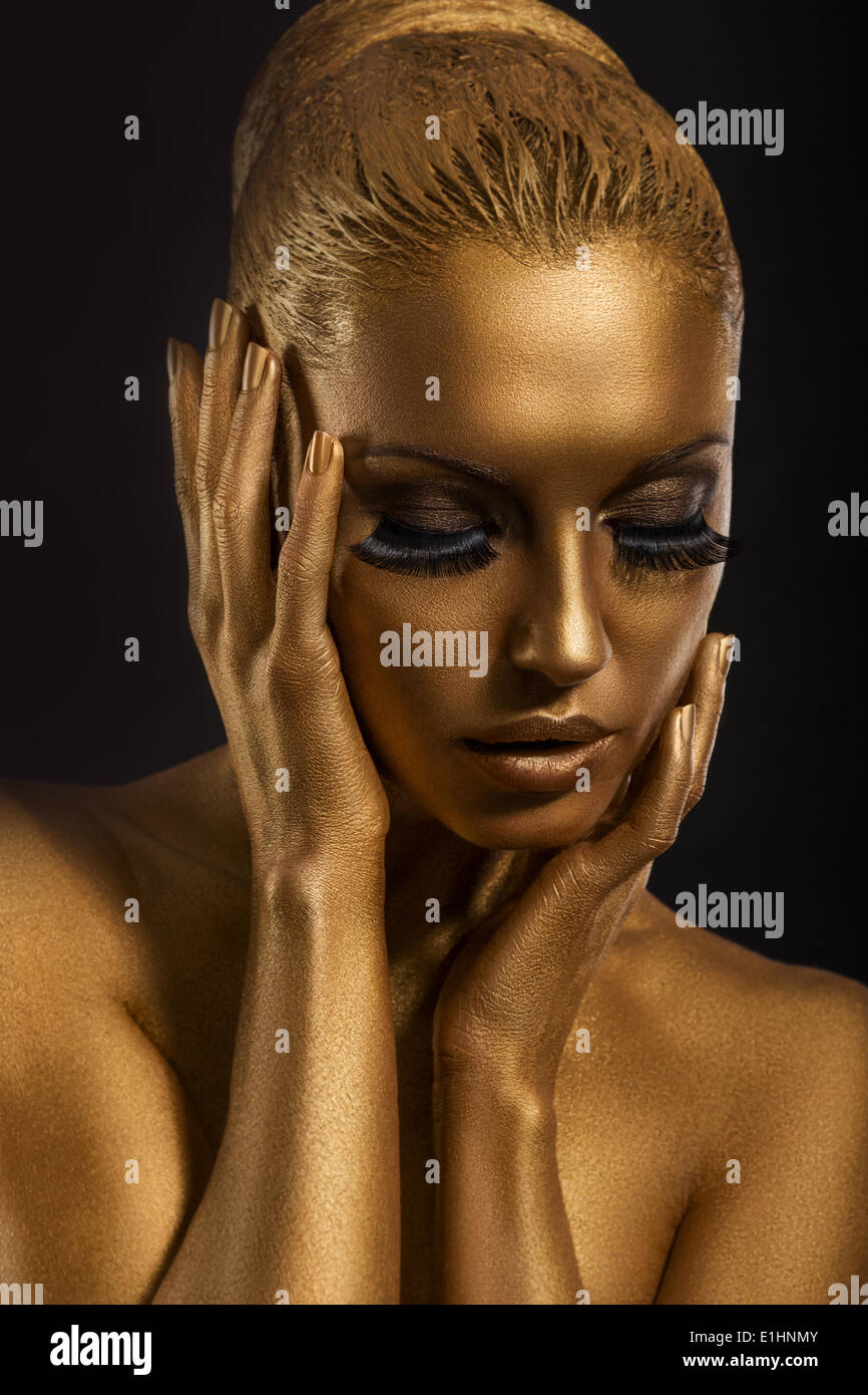 Face Art. Fantastic Gold Make Up. Stylized Colored Woman's Body - Stock Image