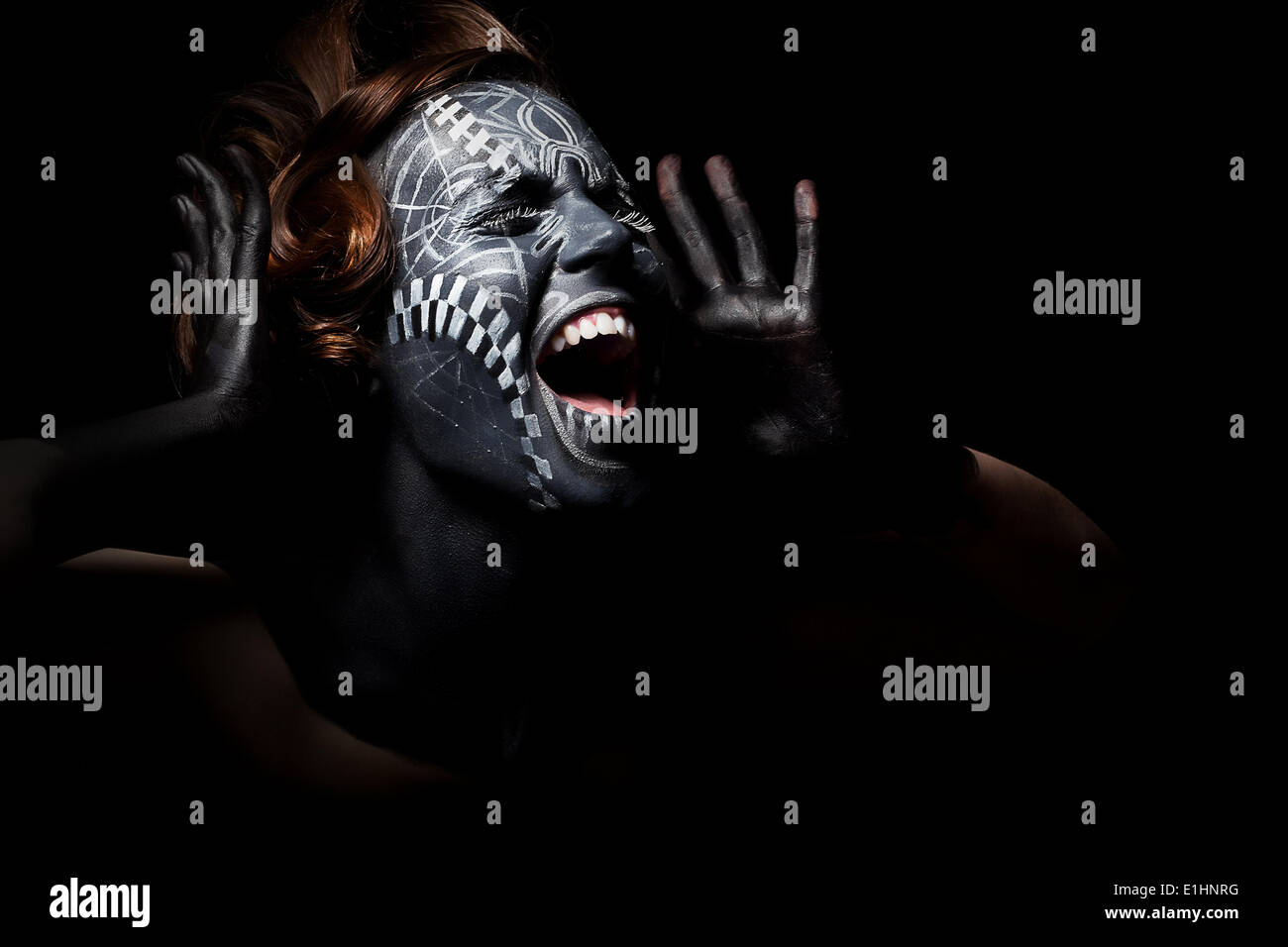 Art photo of a stressed ethnic woman with black painted mask on face and tattoo - Stock Image