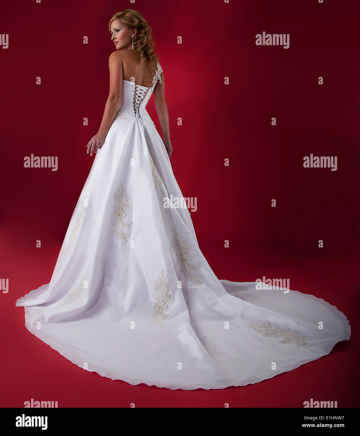 Fashionable blonde young bride in long white wedding dress over red ...