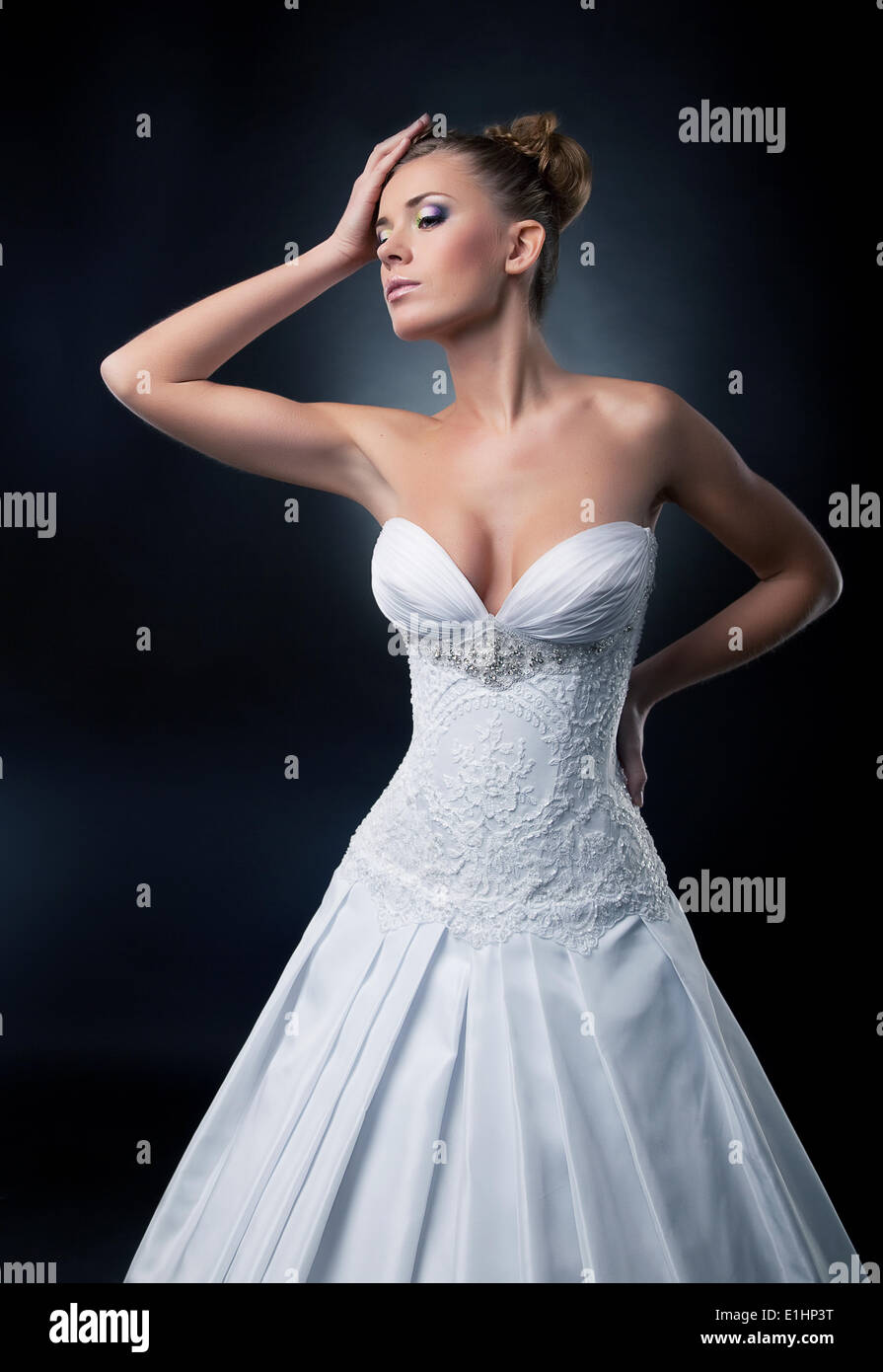 Tempting bride blond hair female fashion model posing in studio. Series of photos - Stock Image