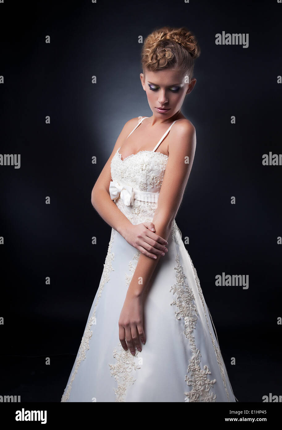 Wedding style - pretty fashionable young bride posing in white bridal dress, studio shot - Stock Image