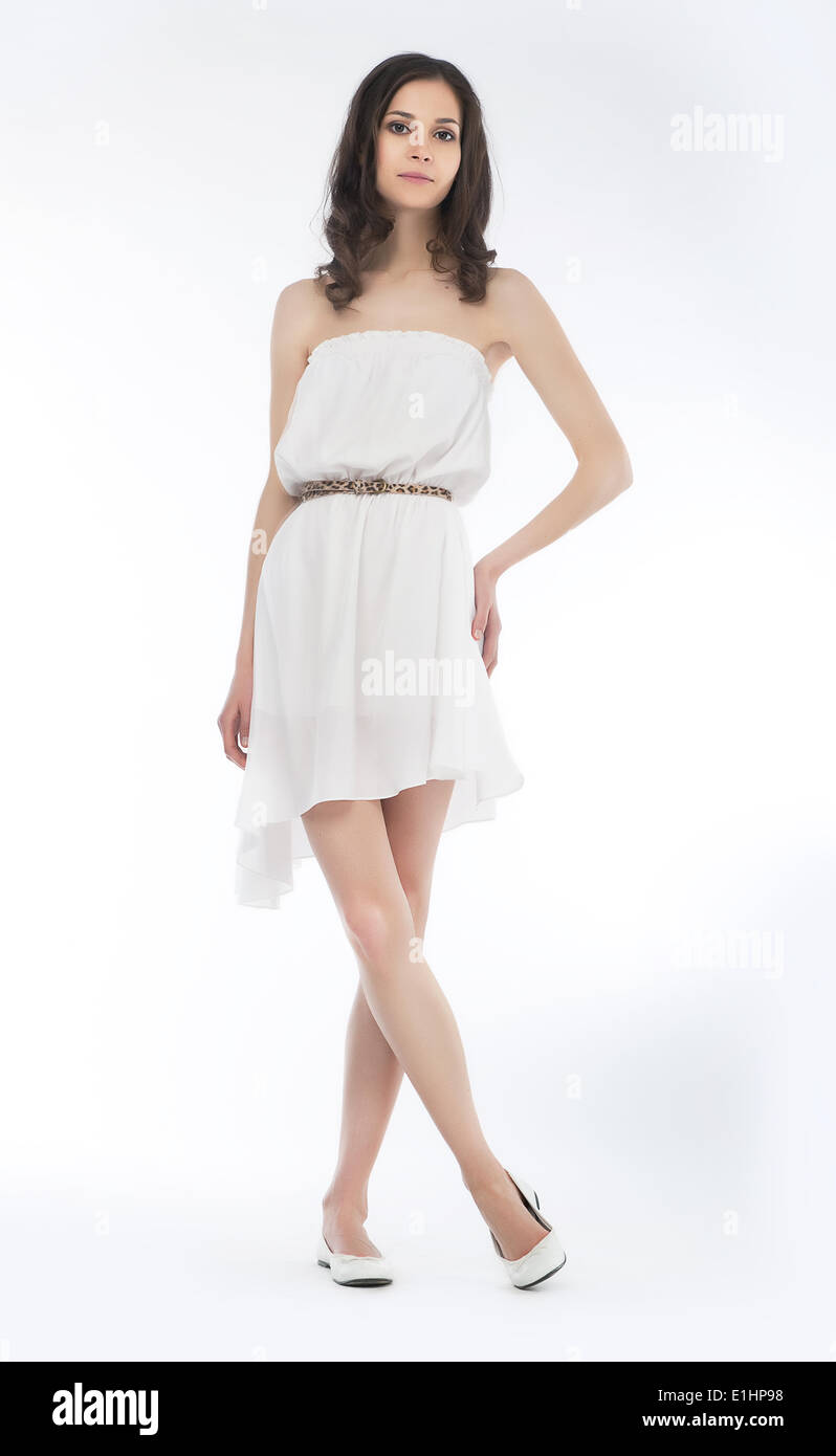 Young charming female in summer dress posing over white background - Stock Image
