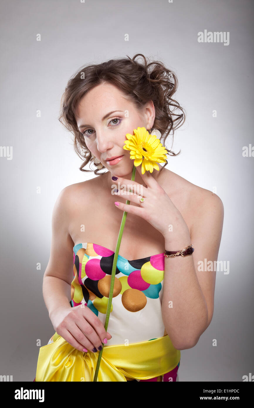 Lovely young female in bright multicolor dress posing with flowers - series of photos - Stock Image