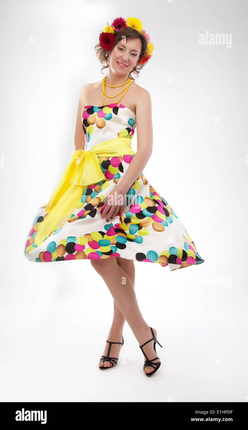 Graceful joyful young girl in colorful spring dress posing - studio shot - Stock Image