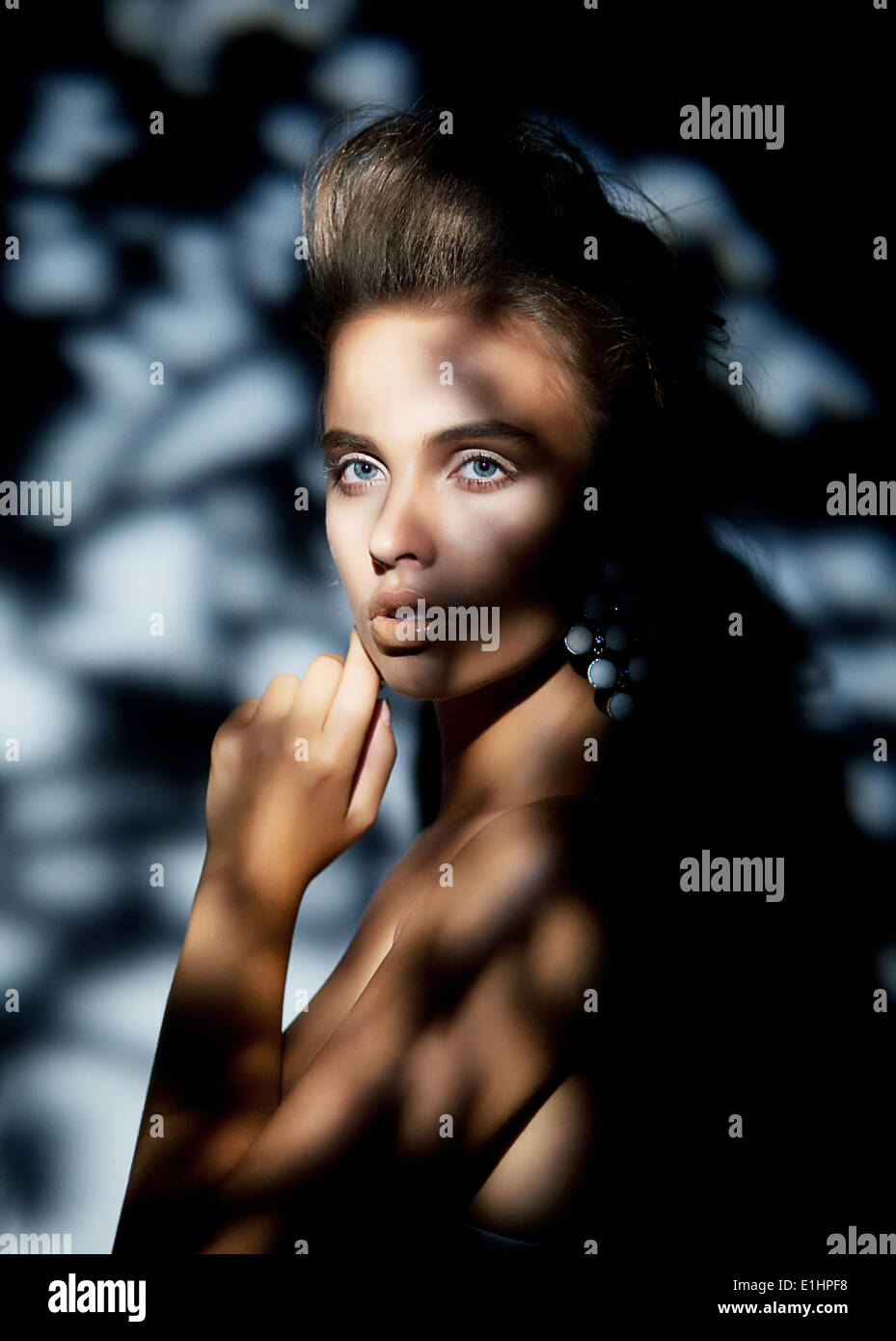 Beautiful female face in blurrs bokeh blue shadows - Stock Image