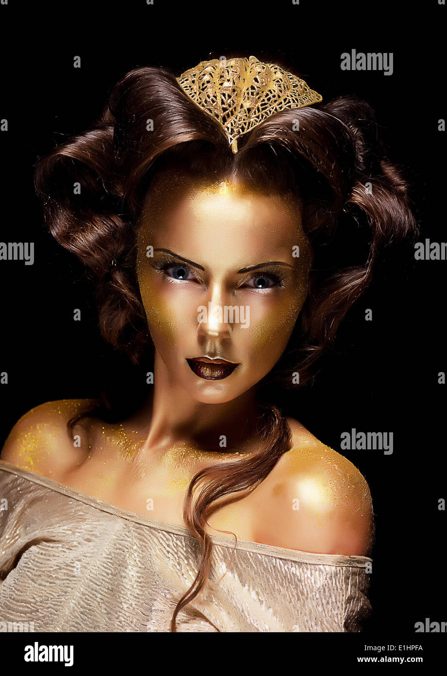 Dramatic style. Woman gilded gold face - theater luxury make up - Stock Image