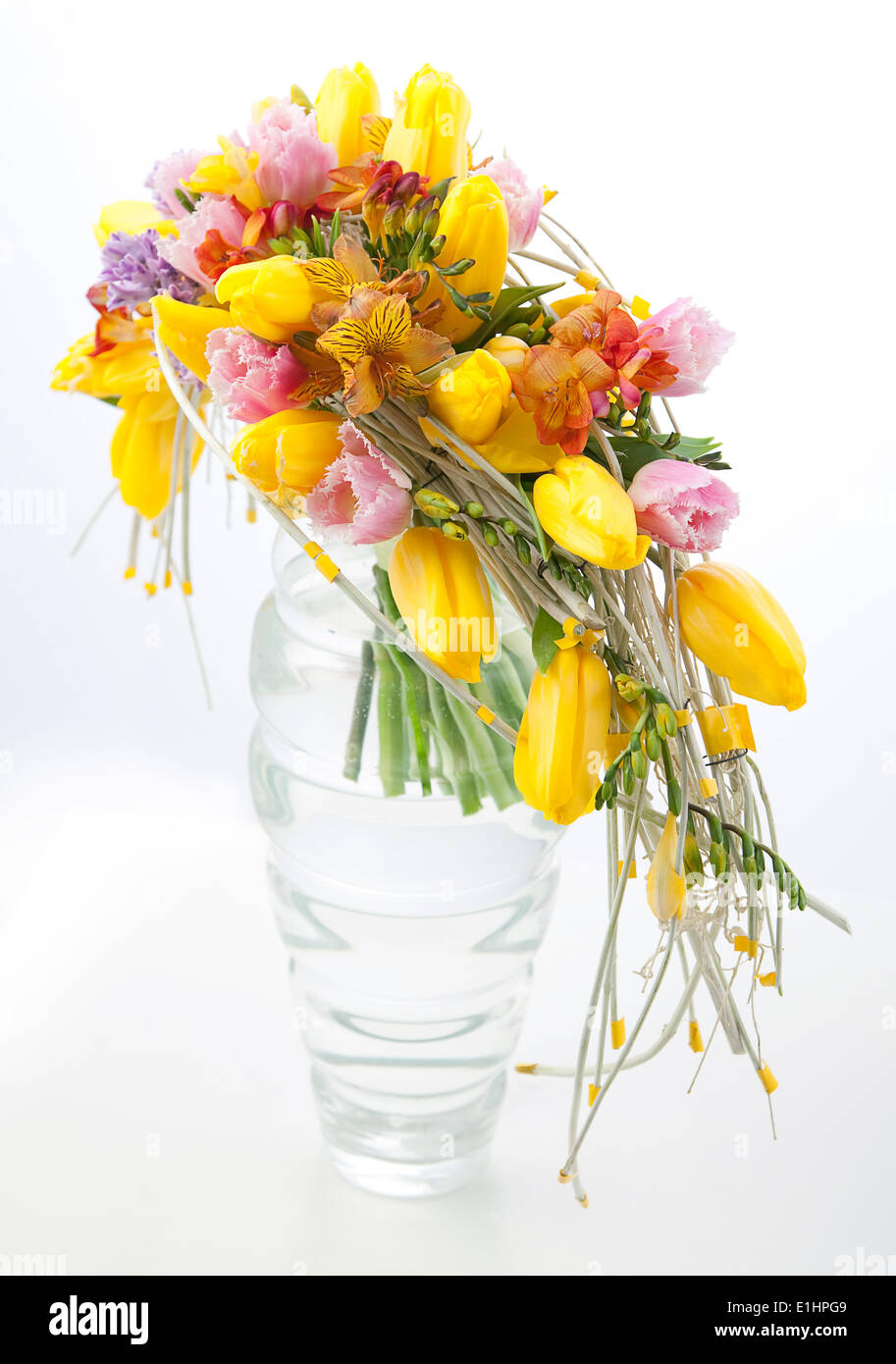 Floristry - colorful flower bouquet arrangement centerpiece in transparent vase isolated on white background - Stock Image