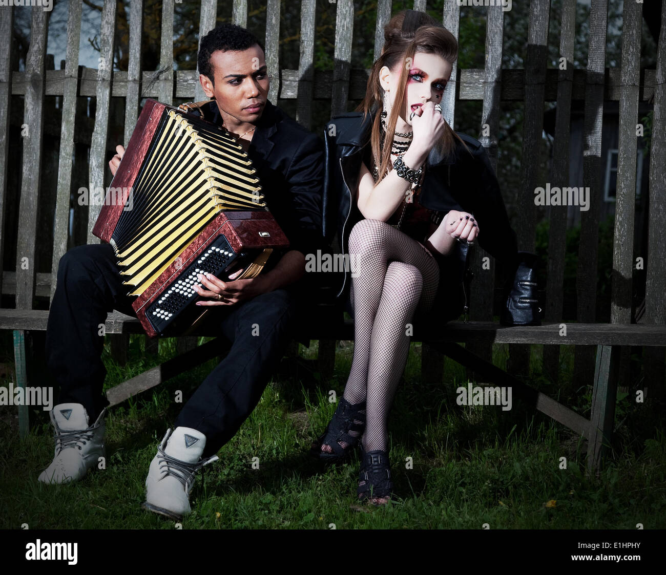 Couple young people - black man and white woman sitting on bench against the fence. Accordion. Countryside. Serenade - Stock Image
