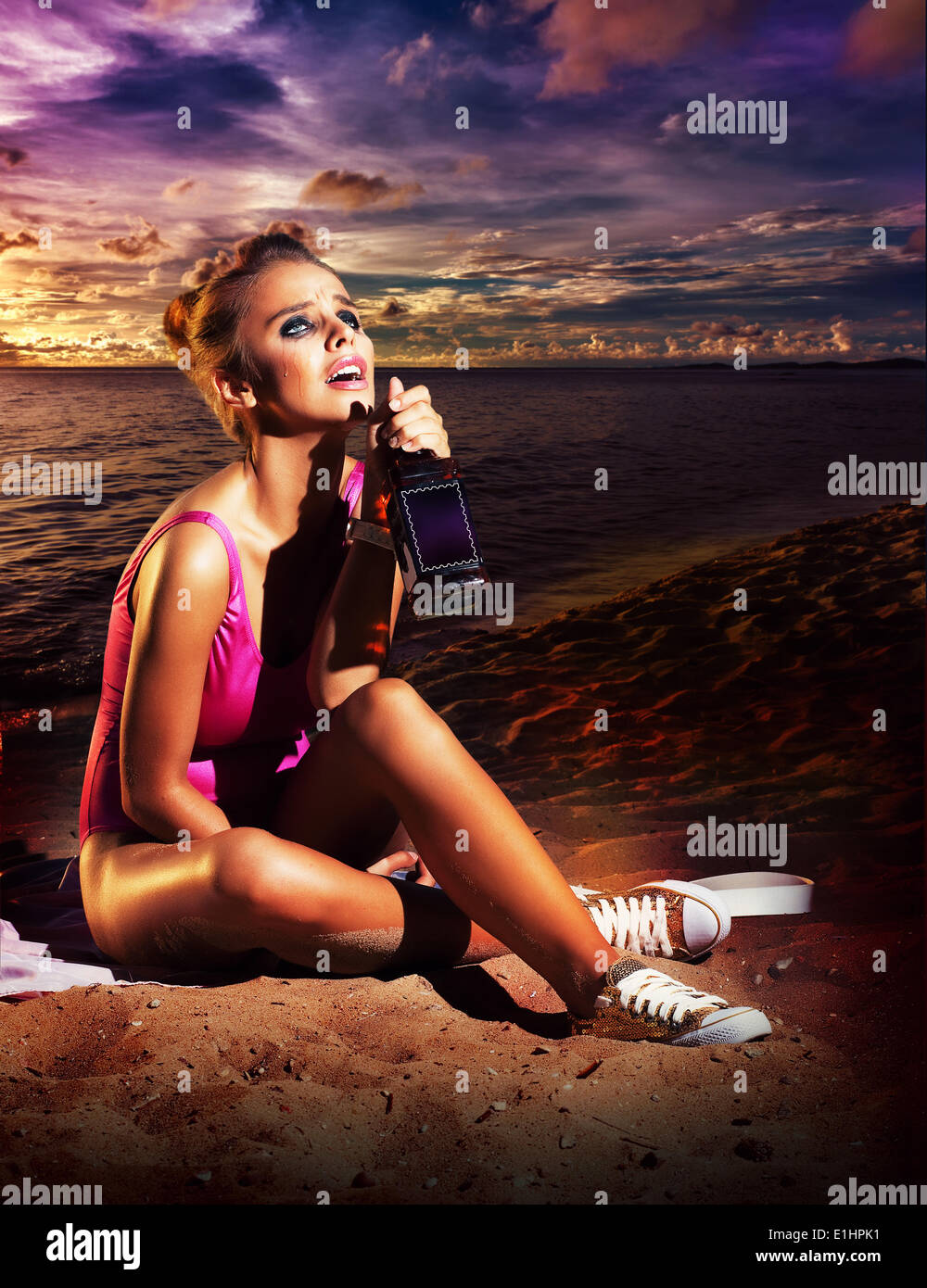 Beautiful young woman drinking booze on beach - alcoholism or other addiction - Stock Image