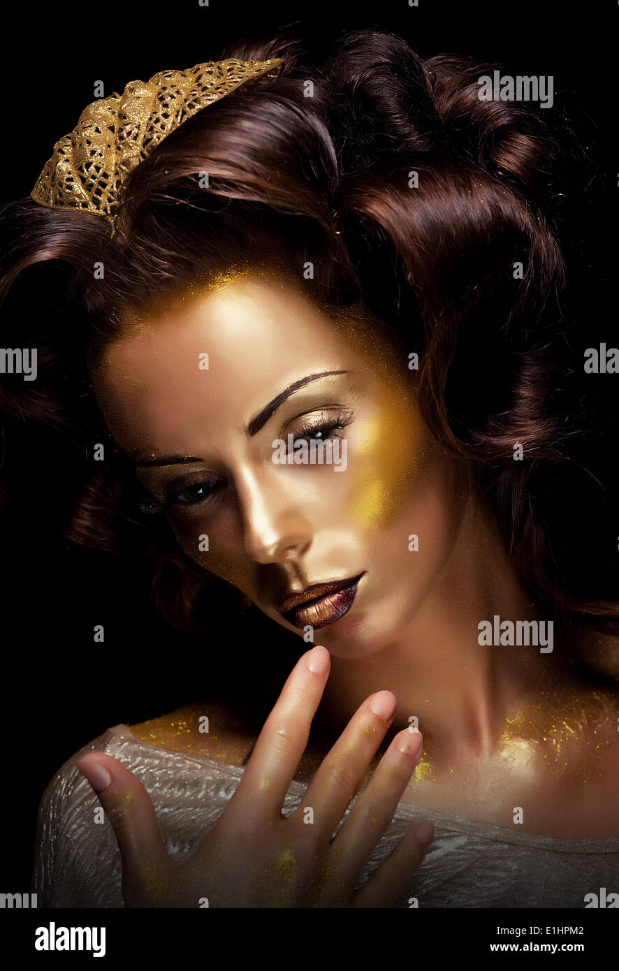 Paint. Fantasy. Glamor. Creative gold make-up, beauty woman face and fashion style - Stock Image