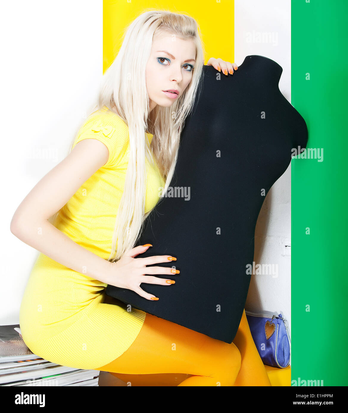 Bright portrait of beautiful blonde female with black mannequin. Studio shot Stock Photo