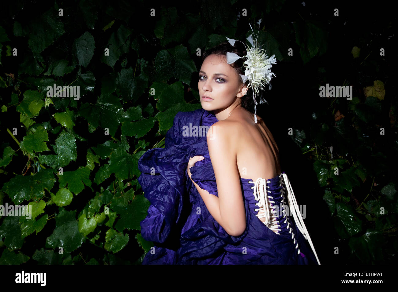Nocturnal scenery - fashionable woman in blue dress among green plants - Stock Image