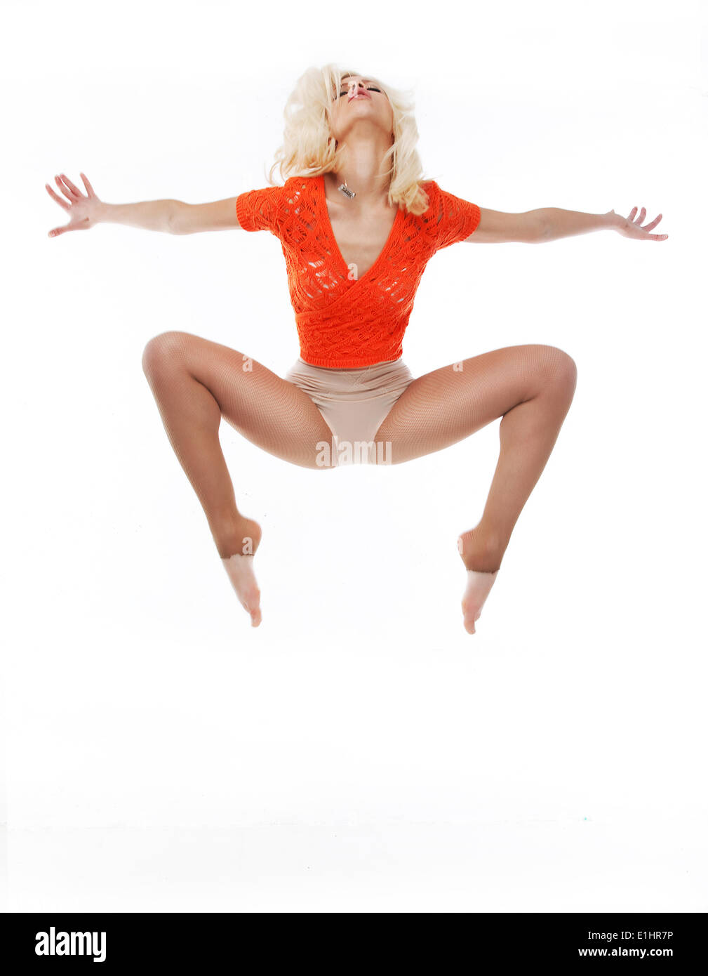 Sporty young fit woman jumping isolated on white background - Stock Image