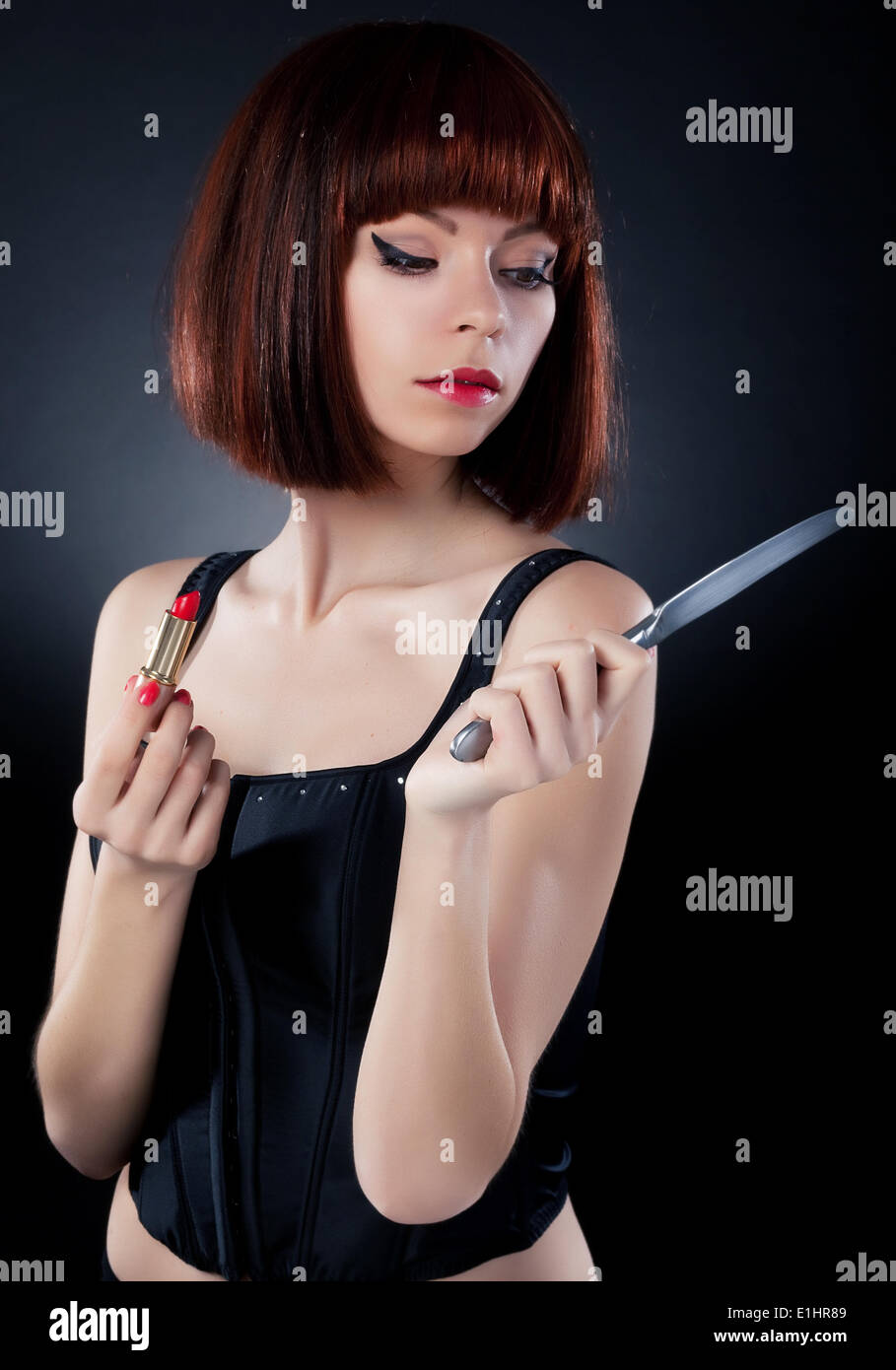 Beautiful girl in red hair wig putting on make up - reflects on table knife Stock Photo