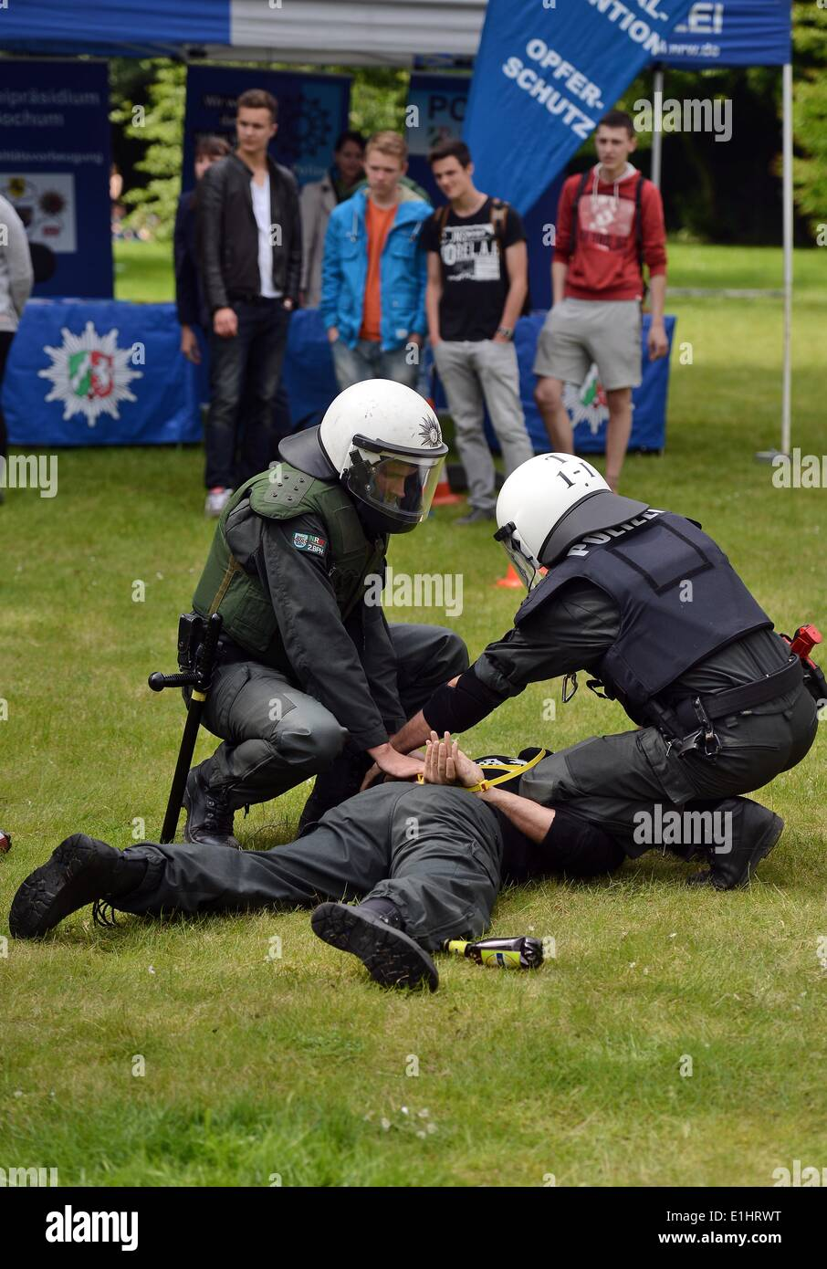 Bochum, Germany. 2nd June, 2014. Visitors look an as two police officer stage an arrest during a recruitment campaign of North Rhine-Westphalia's police force in Bochum, Germany, 2 June 2014. North Rhine-Westphalia's police force is currently recruiting 1500 new officers. Photo: Henning Kaiser/dpa/Alamy Live News - Stock Image