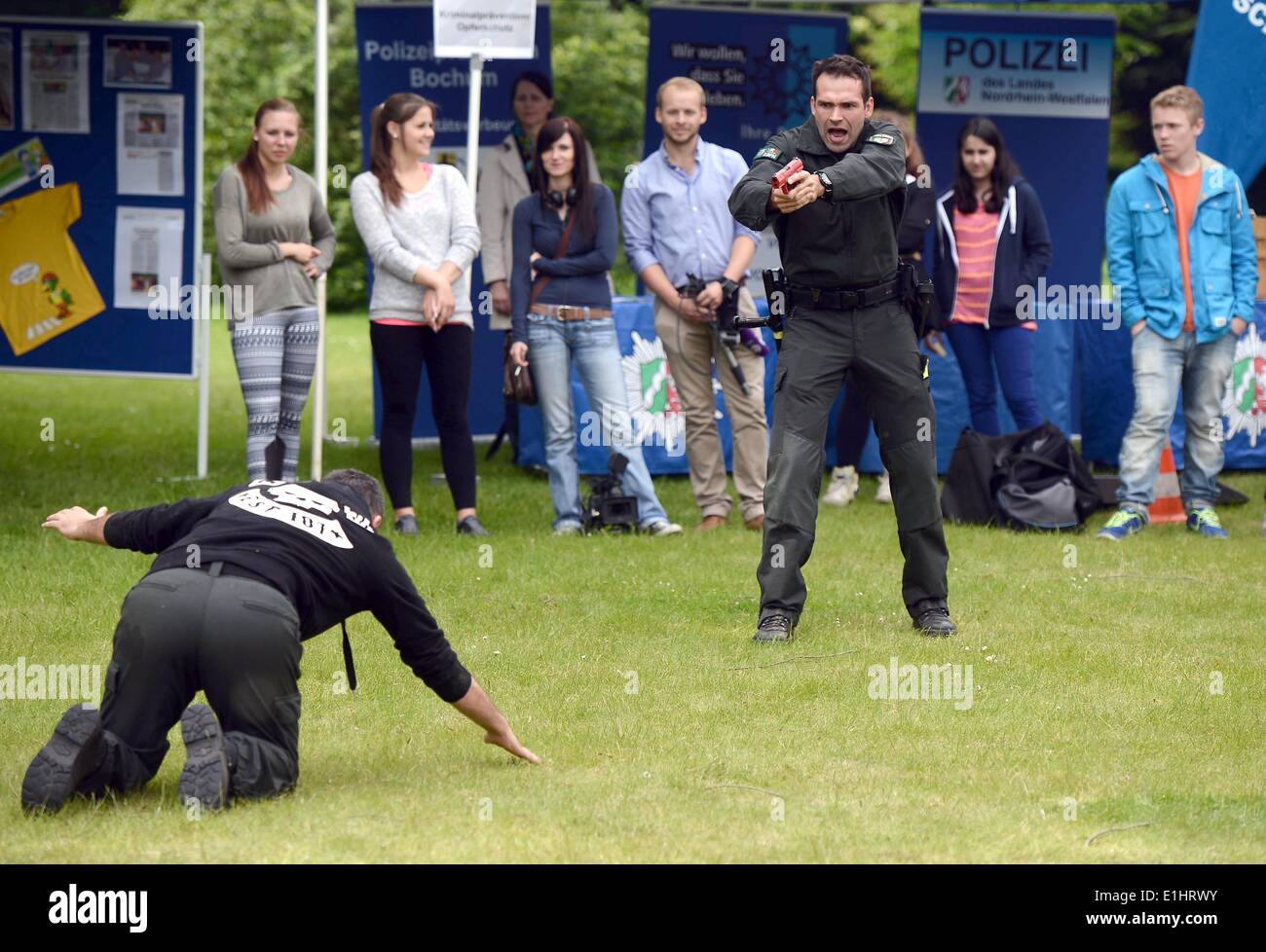 Bochum, Germany. 2nd June, 2014. Visitors look an as two police officers (front) stage an arrest during a recruitment campaign of North Rhine-Westphalia's police force in Bochum, Germany, 2 June 2014. North Rhine-Westphalia's police force is currently recruiting 1500 new officers. Photo: Henning Kaiser/dpa/Alamy Live News - Stock Image