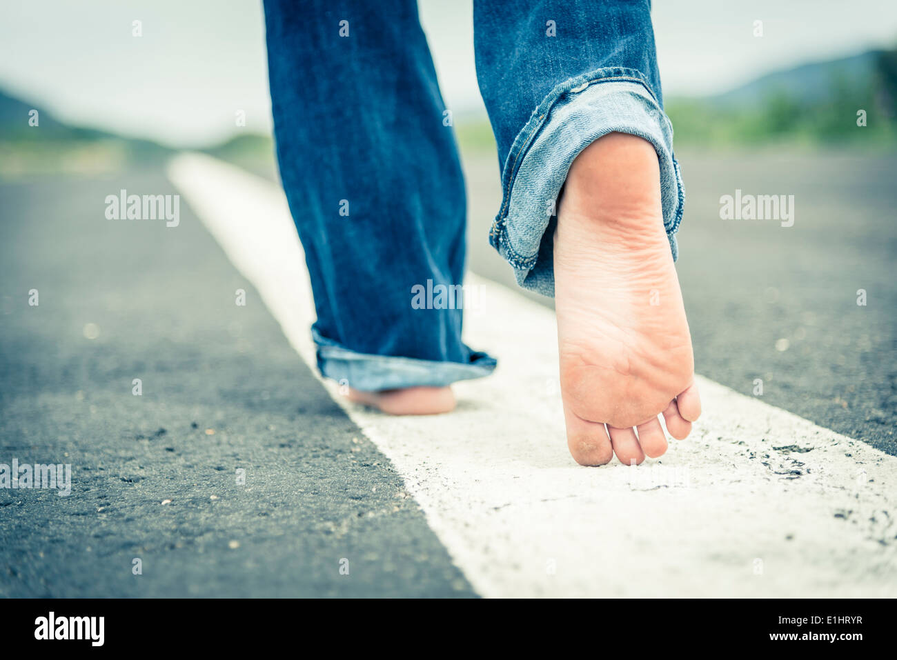 Young woman walking barefoot on centre line of empty street, partial view - Stock Image