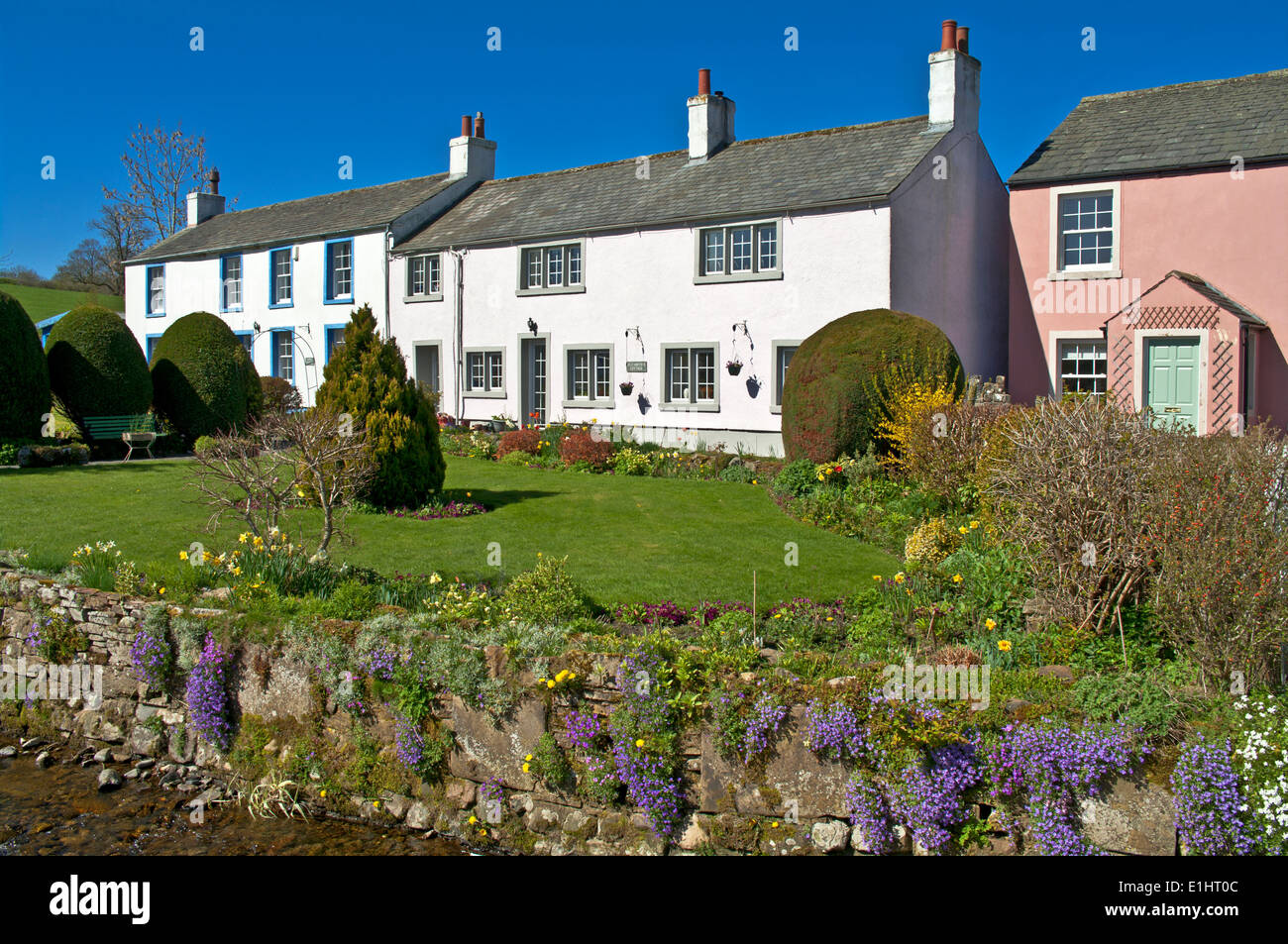 Traditional old painted cottages with pretty gardens in the village of Caldbeck, Cumbria, Lake District National Park England Uk - Stock Image