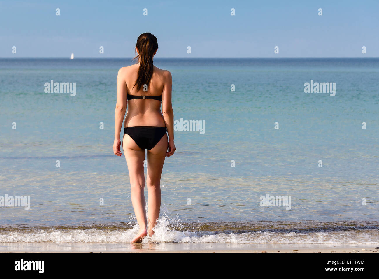 Young woman with a lovely figure entering the sea - Stock Image