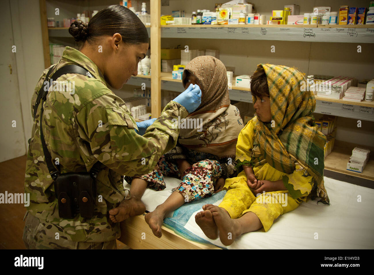 An Afghan girl, right, watches as a U.S. Marine, left, gives her sister cough suppressant in Herat province, Afghanistan, Feb. - Stock Image