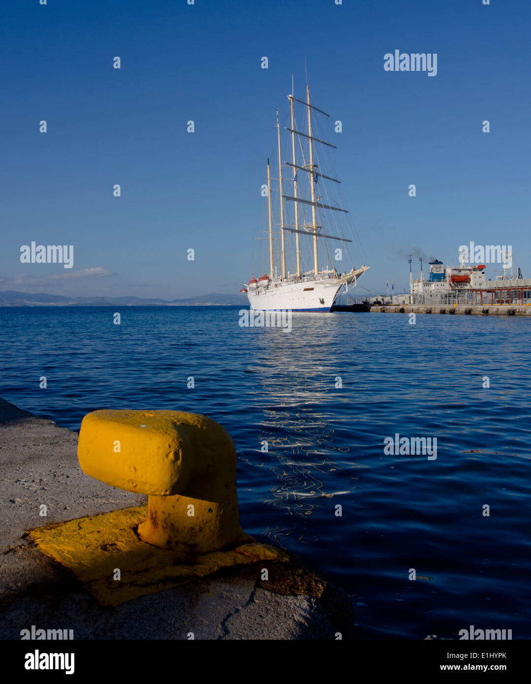 View across Kos Town port towards a square rigged yacht. - Stock Image