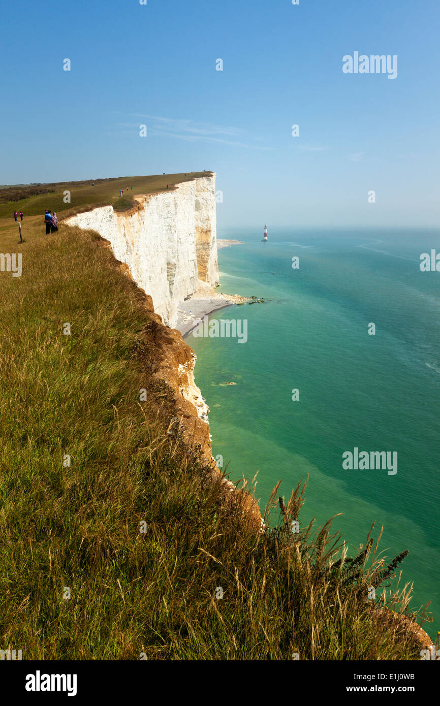 Tourists on the edge of Beachy Head cliff on the Channel coast, East Sussex, UK - Stock Image