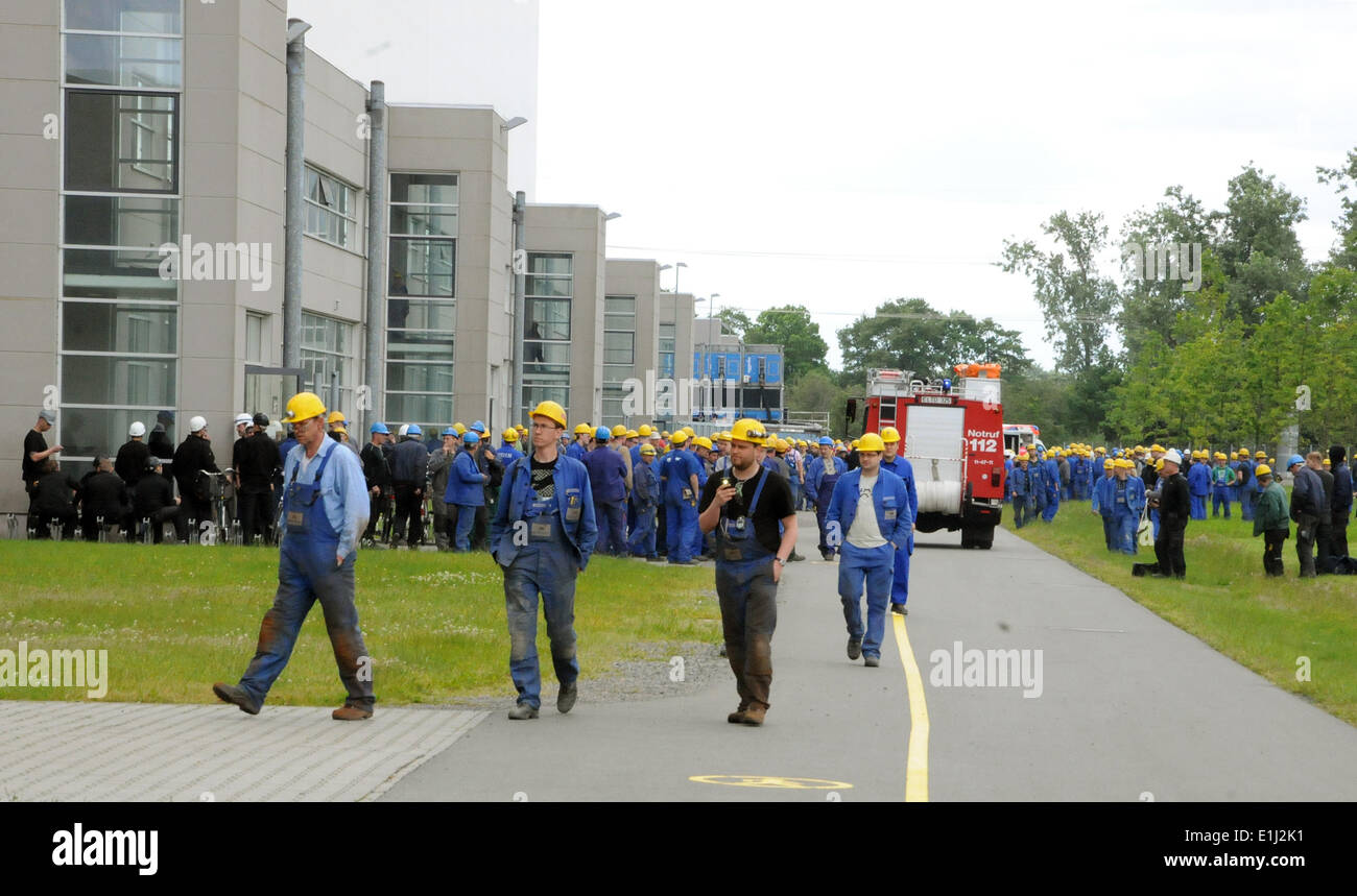 Papenburg, Germany. 02nd June, 2014. Evacuated shipyard employees stands at Meyer Werft shipyards in Papenburg, Germany, 02 June 2014. A fire broke out this morning in a row of cabins on the cruise ship 'Quantum of the Seas,' which is under construction at the shipyards. The fire was brought under control and extinguished quickly. Photo: CHRISTOPH ASSIES/dpa/Alamy Live News - Stock Image