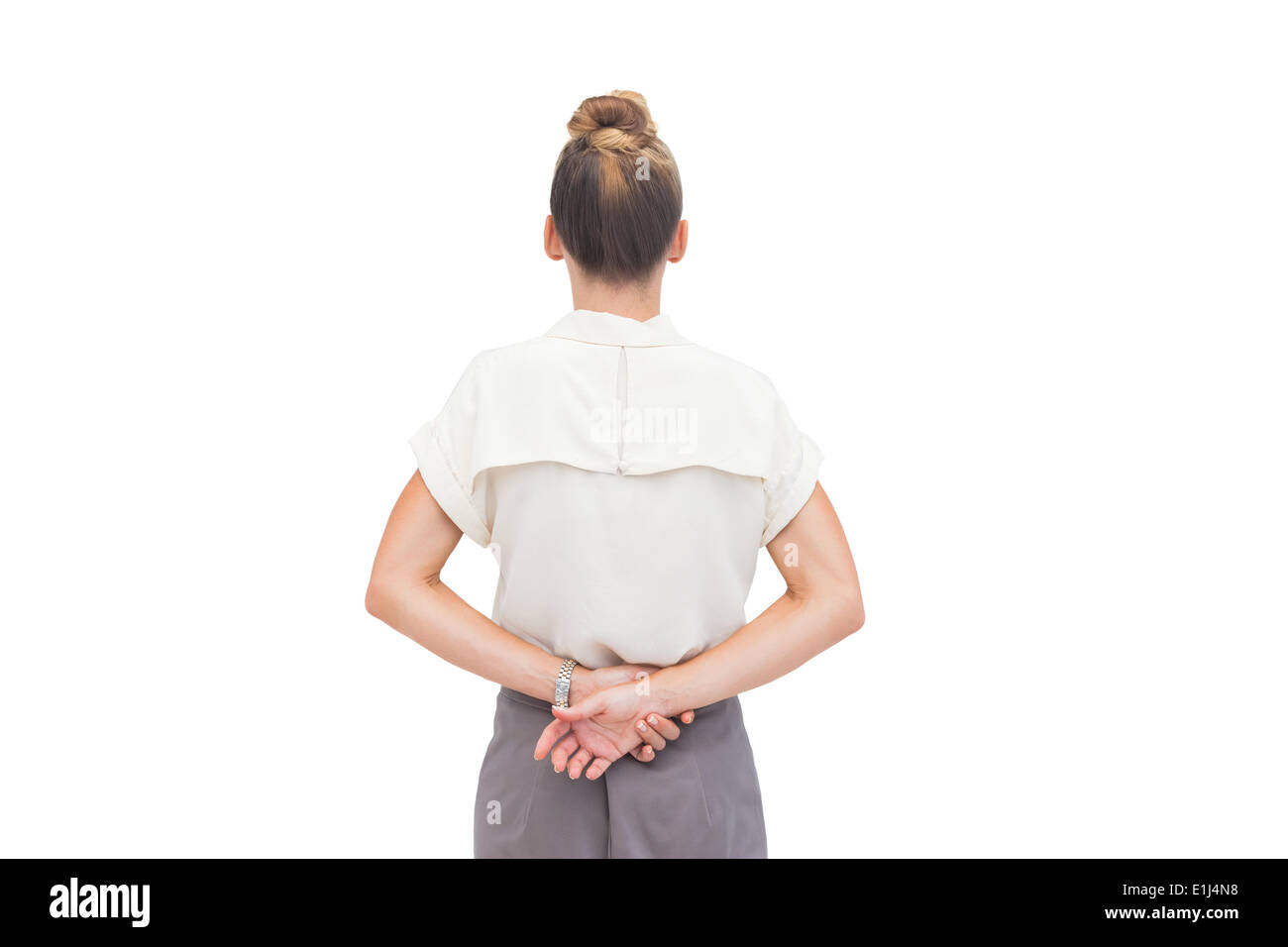 Businesswoman with hands behind her back - Stock Image