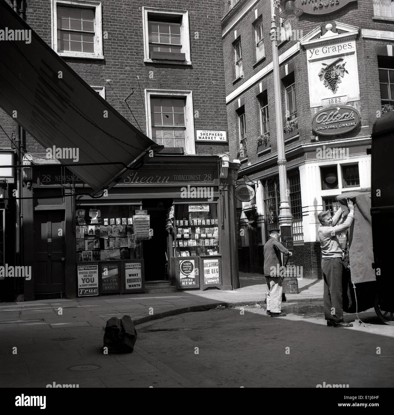 1950s historical picture showing corner shop, a newsagent and an old (1882) Victorian pub, Ye Grapes in Mayfair, Shepherd's Market, London, W1, England. - Stock Image