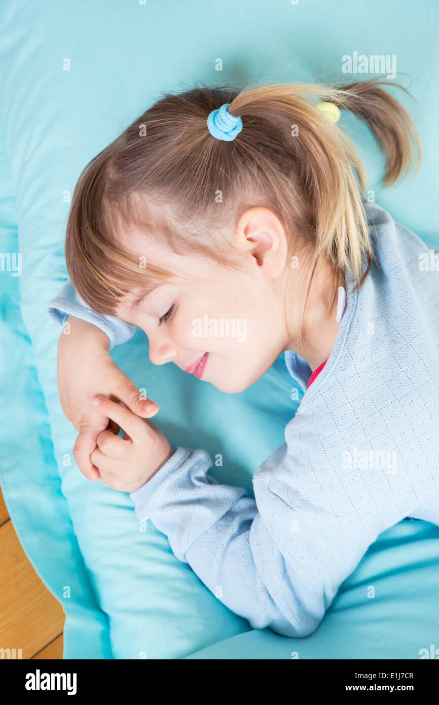 Portrait of little girl sleeping on bean bag, elevated view Stock Photo