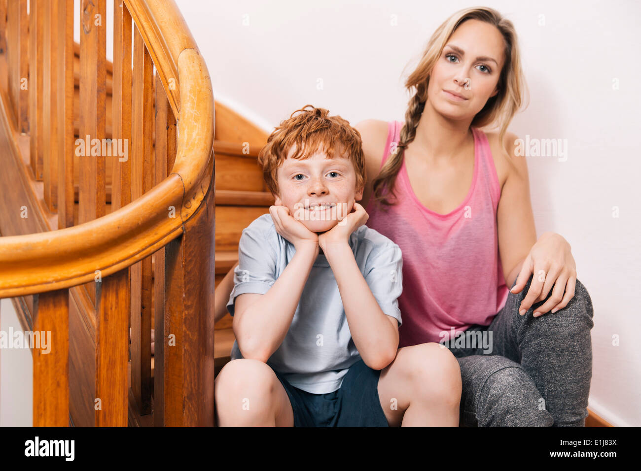 Portrait of mother and son sitting on stairs of their house Stock Photo