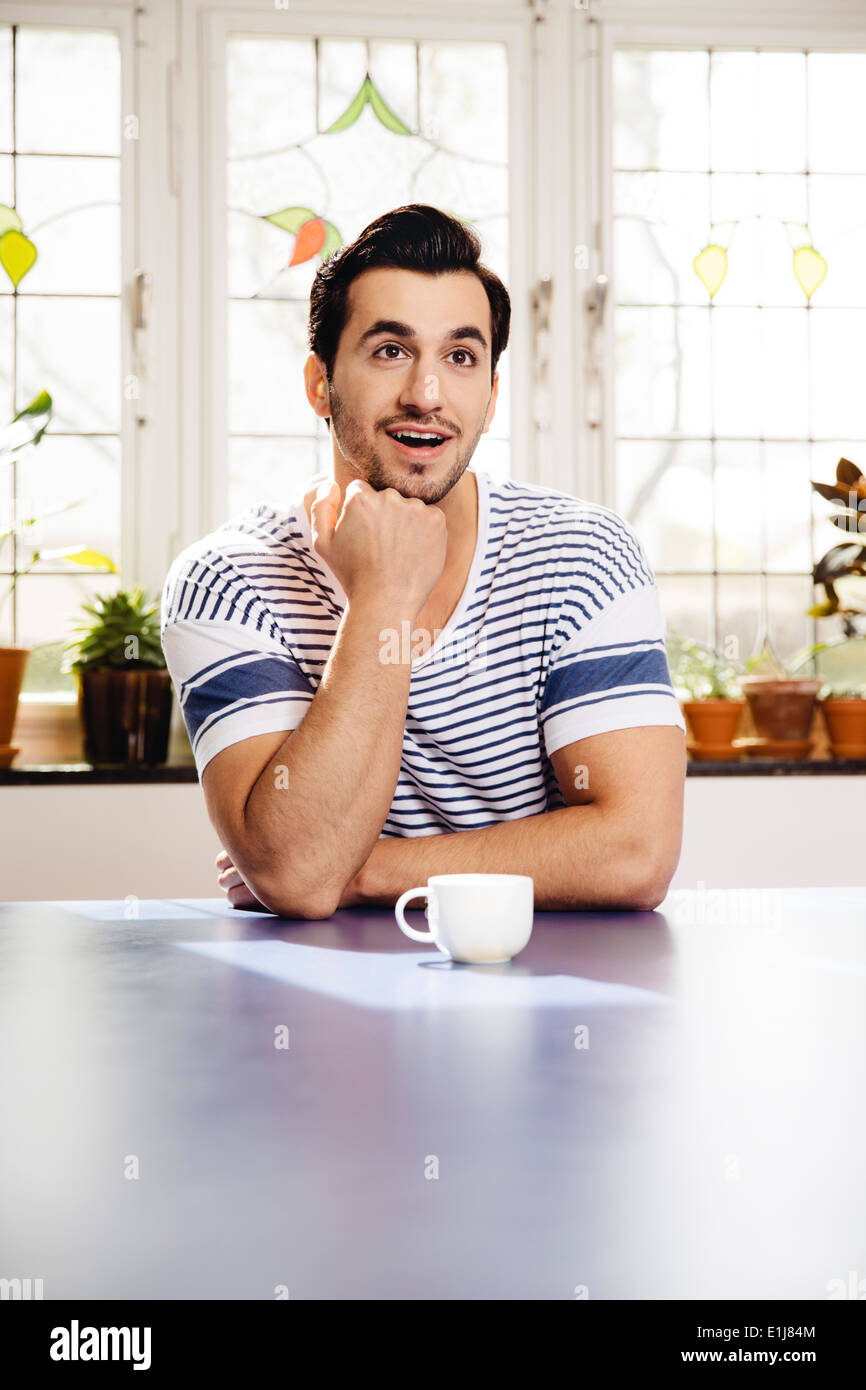 Portrait of astonished young man sitting at blue table with a cup - Stock Image