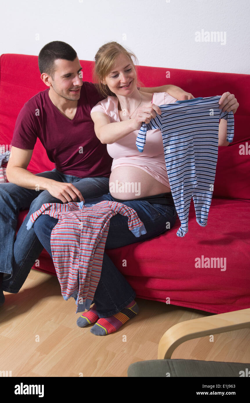 Couple expecting a baby watching rompers at home - Stock Image