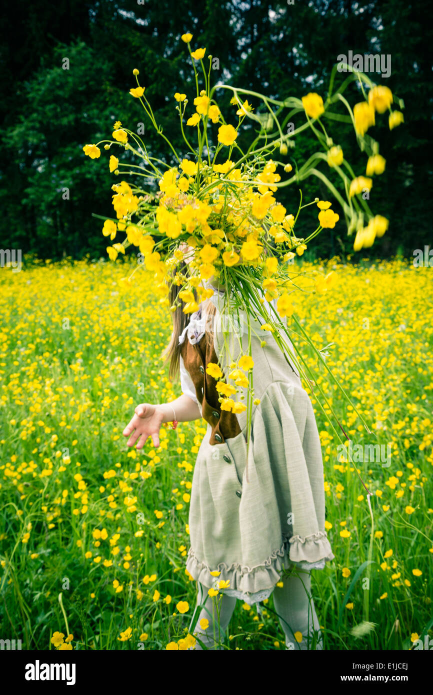 Little girl wearing country style dress throwing buttercups, Ranunculus, in the air - Stock Image