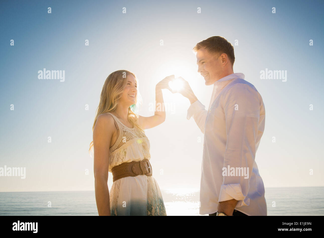 Young couple making a heart in front of sun with hands - Stock Image
