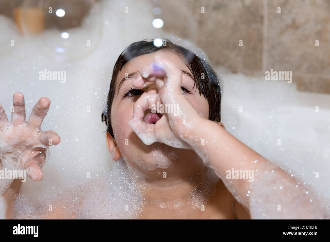 Young boy blowing bubbles in bubble bath Stock Photo