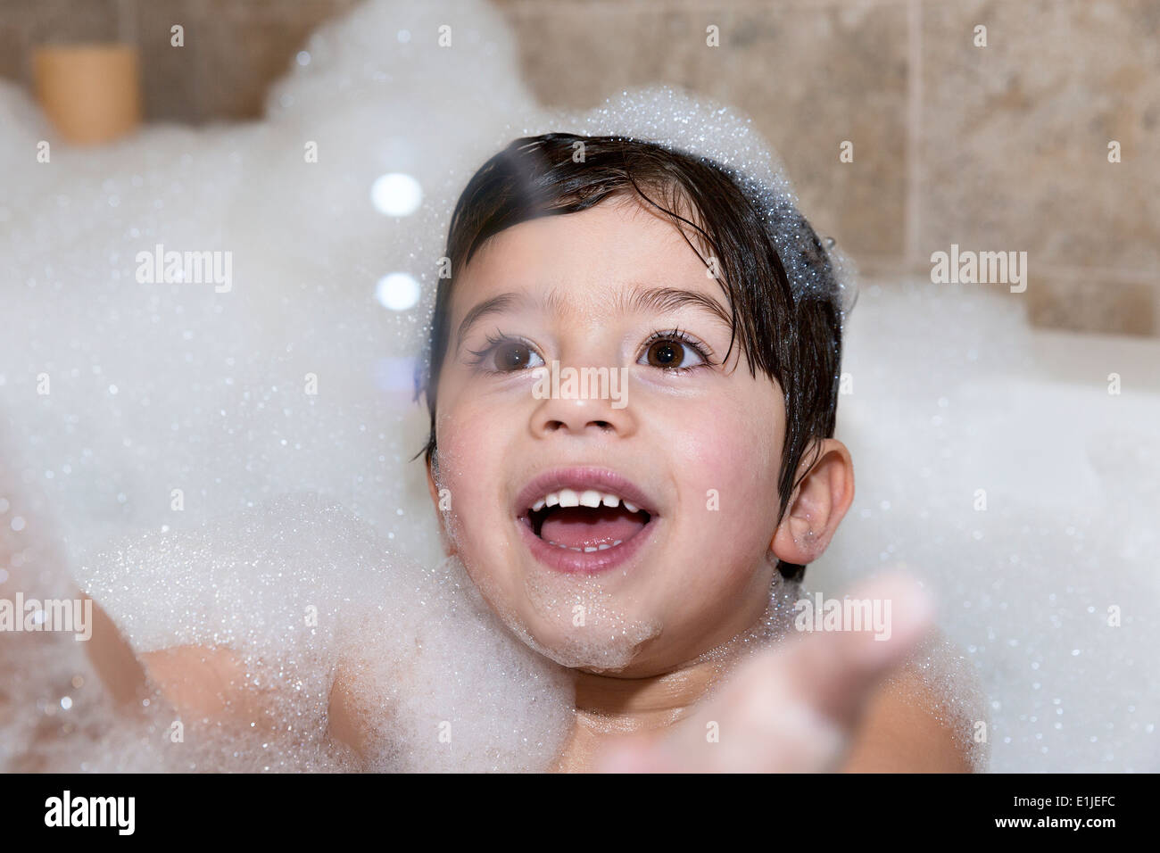 Young boy trying to catch bubble in bubble bath - Stock Image
