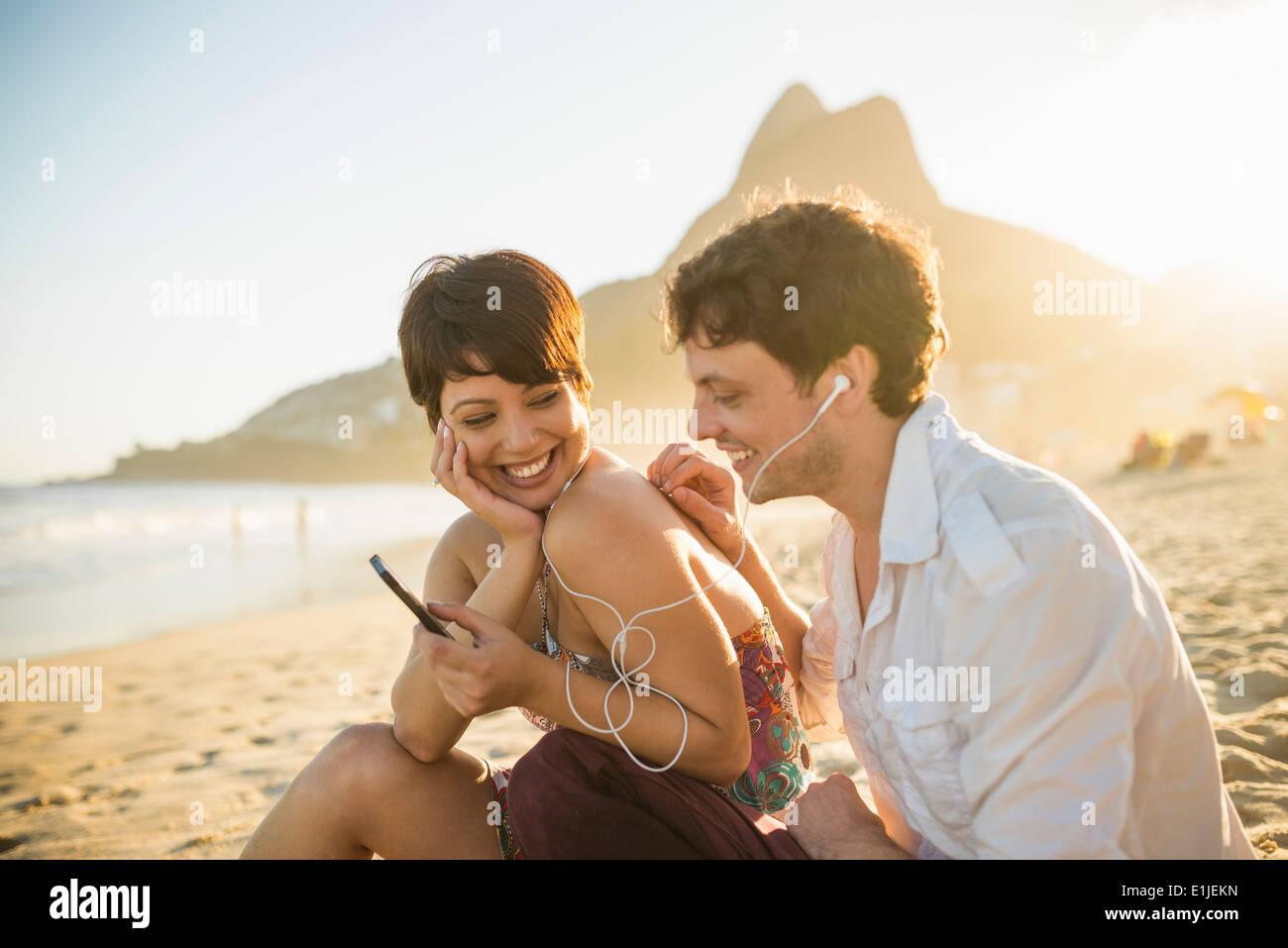 Young couple listening to music, Ipanema Beach, Rio, Brazil - Stock Image