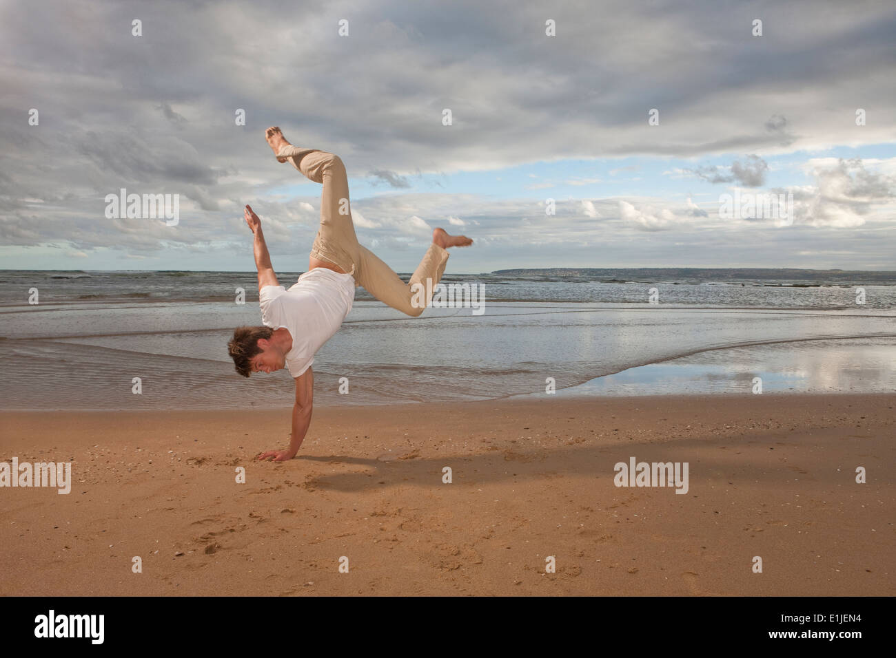 Young man doing handstand on beach - Stock Image