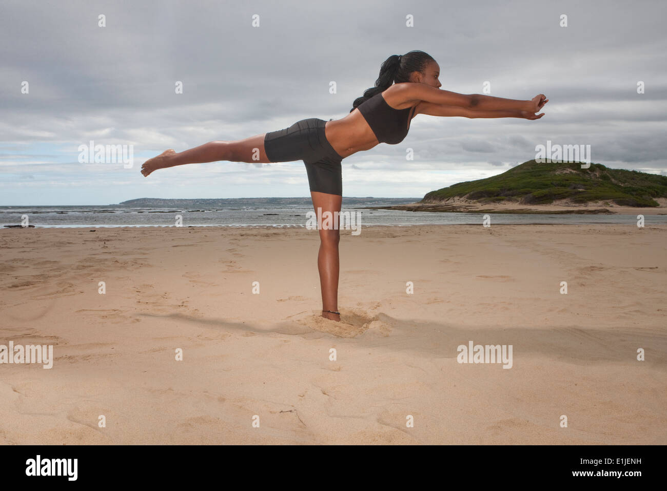 Young woman practicing yoga on one leg at beach - Stock Image