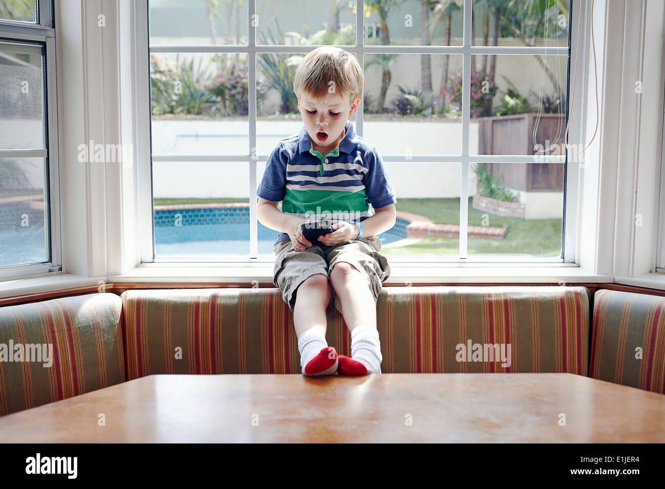 Boy playing handheld video game Stock Photo