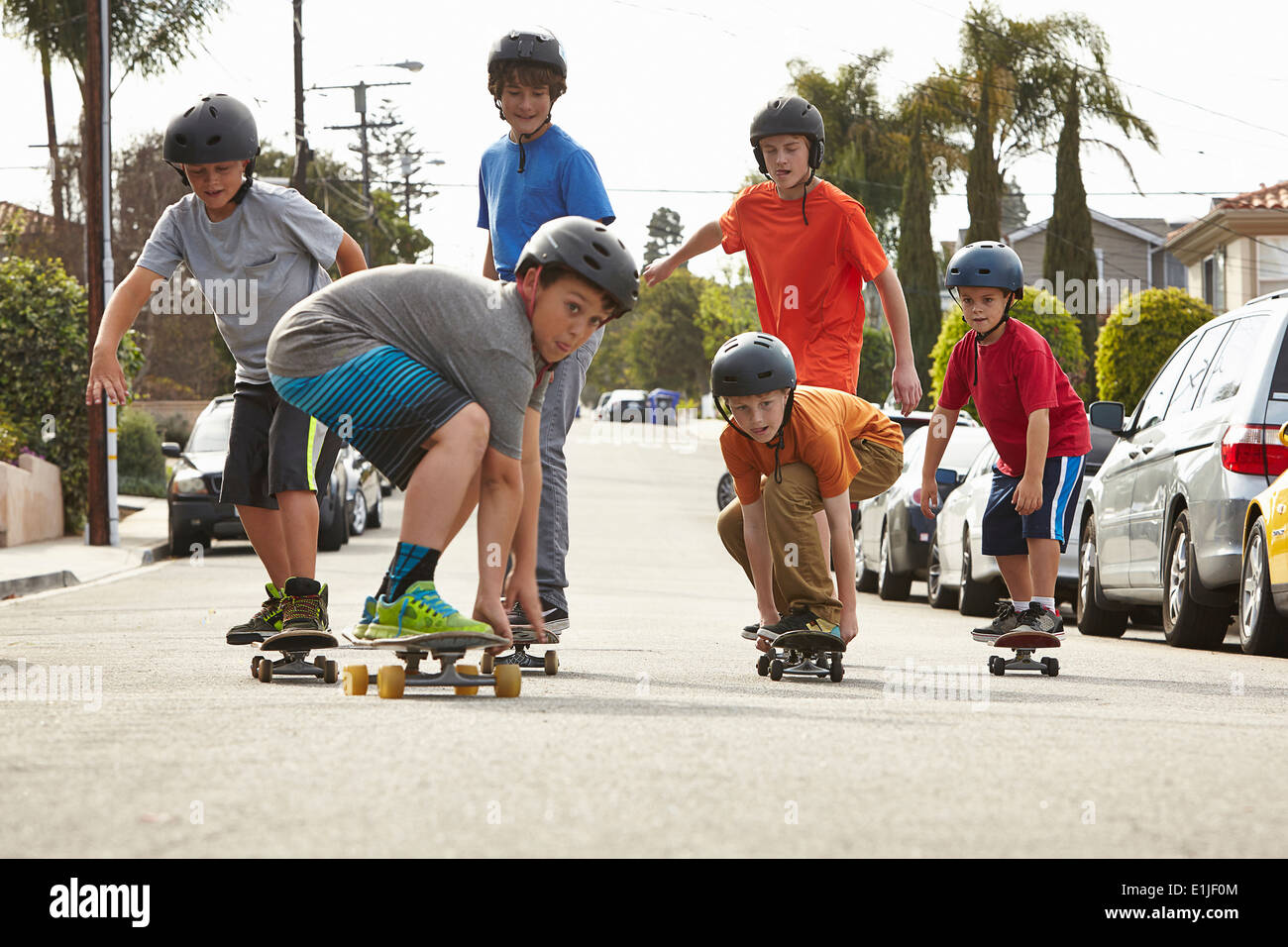 Boys skateboarding on road - Stock Image