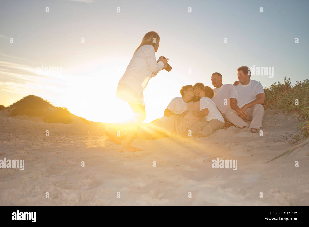 Photographer taking family portrait on beach, Cape Town, South Africa - Stock Image