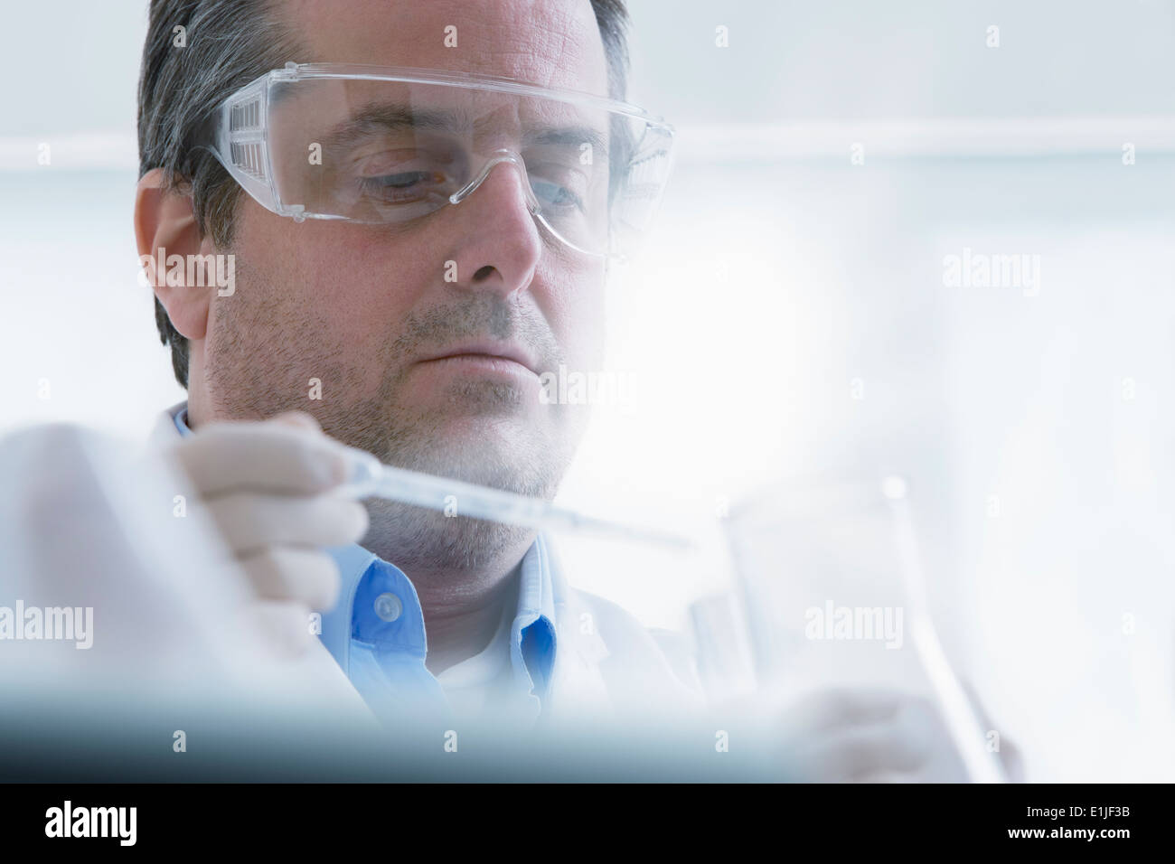 Scientist holding dropper and test tube - Stock Image