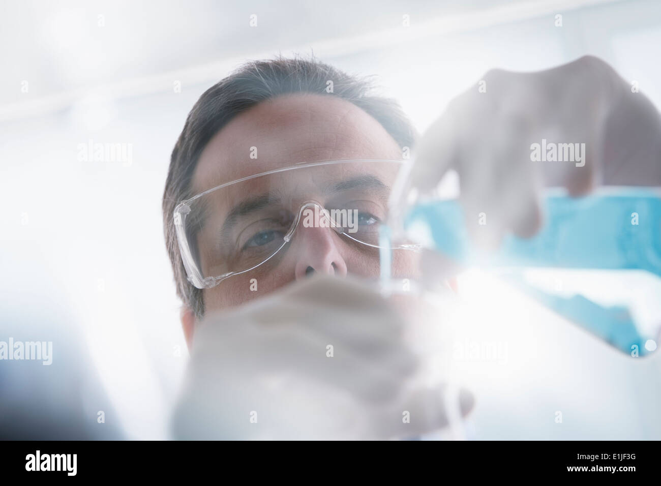 Scientist pouring liquid into test tube - Stock Image