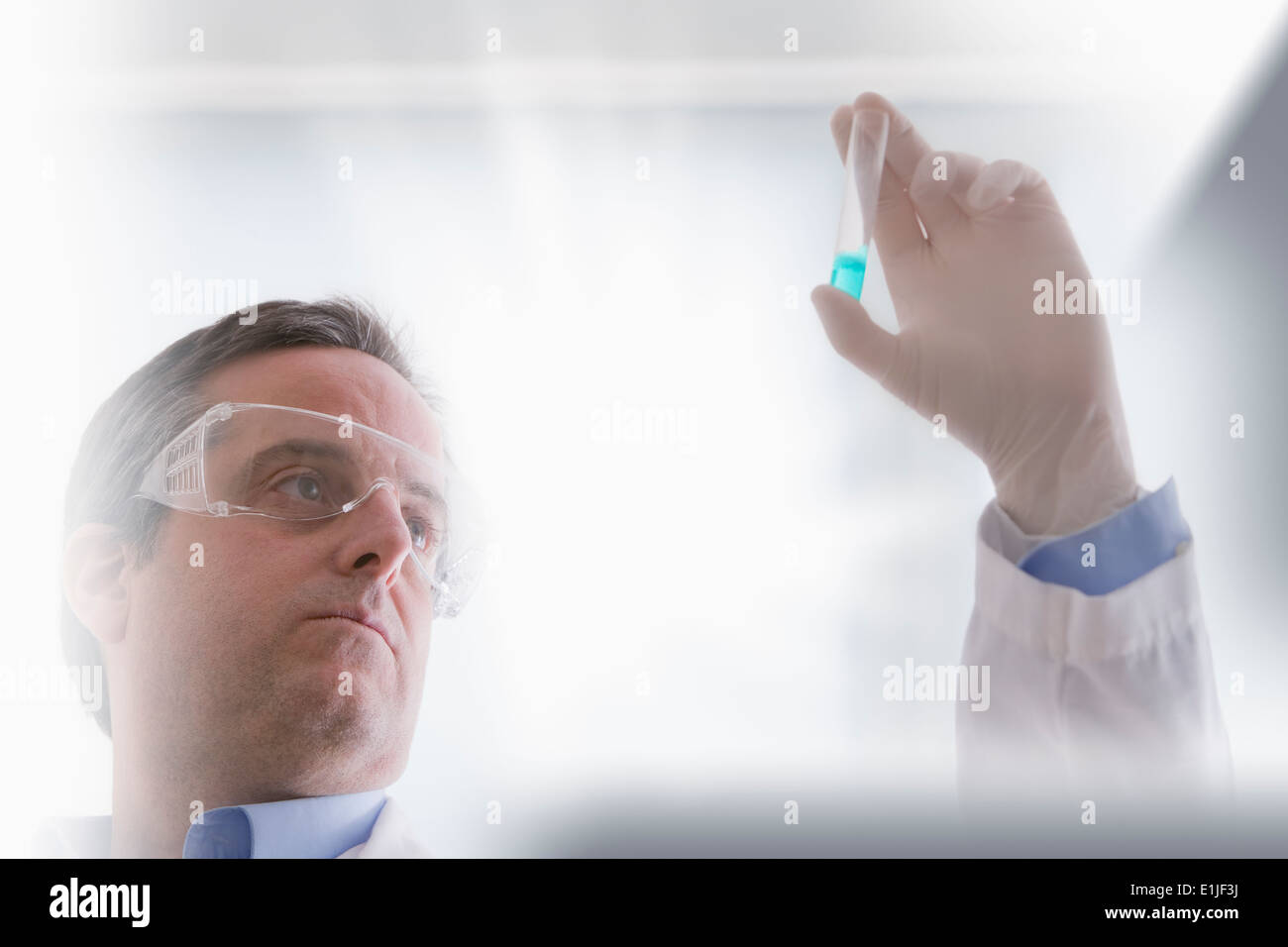 Scientist looking at test tube - Stock Image