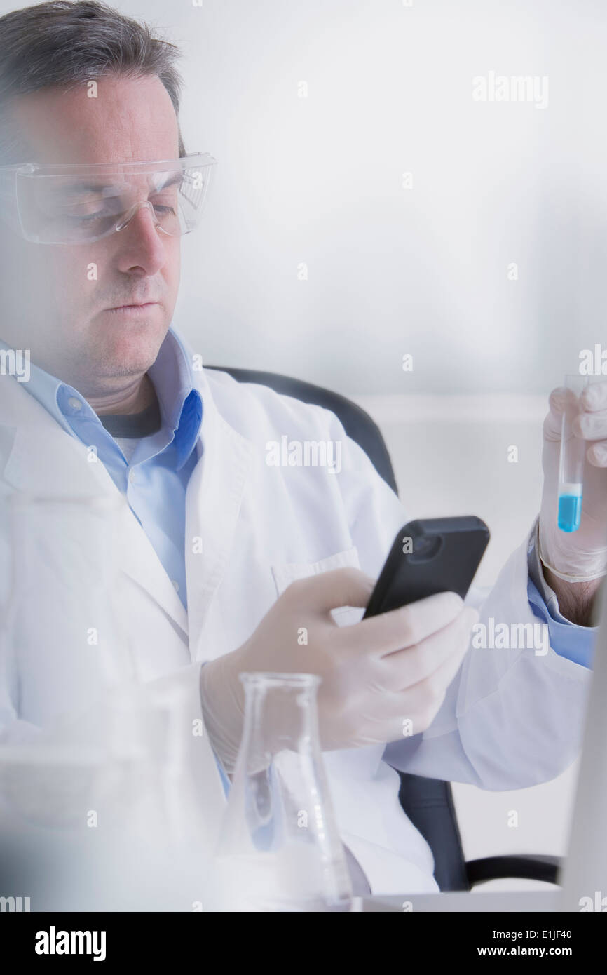 Scientist holding smartphone and test tube - Stock Image