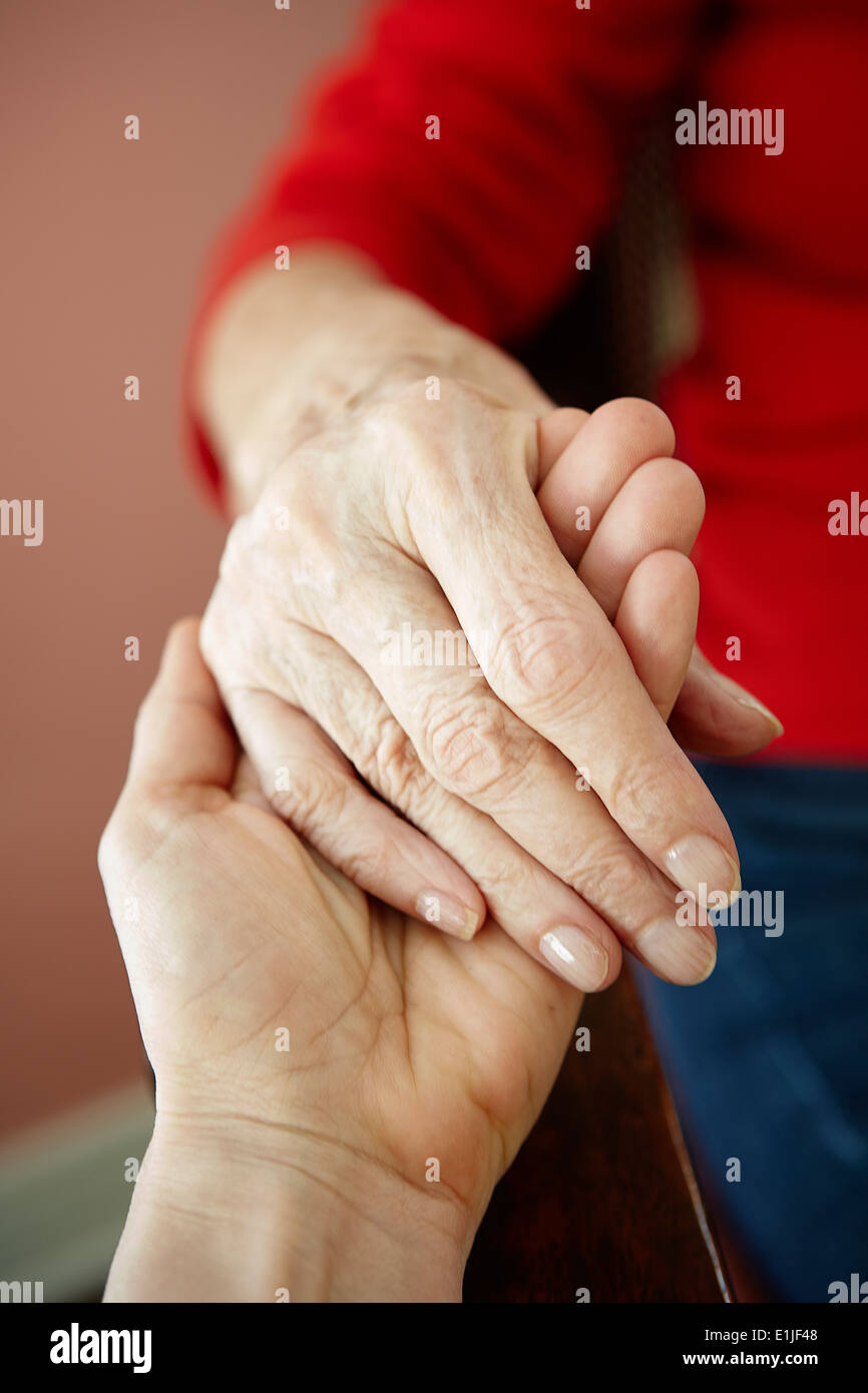 Close up of mature woman holding 82 year old grandmothers hand - Stock Image