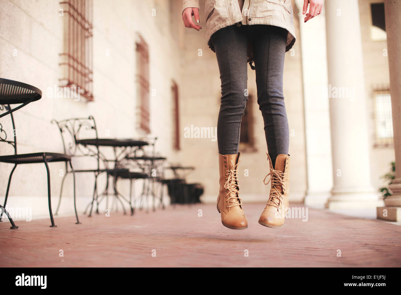 Young woman waist down jumping next to sidewalk cafe - Stock Image